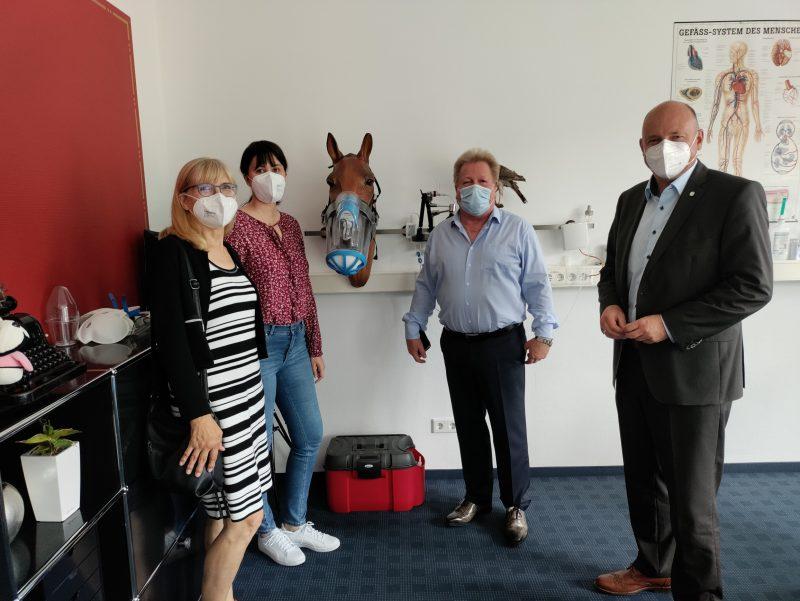 Vier Personen mit Masken vor einem Inhalationsgerät